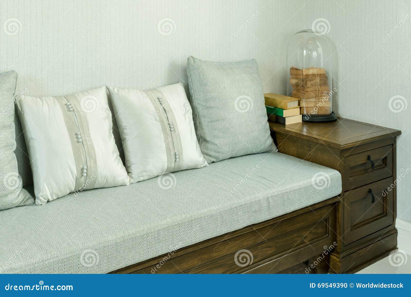 Woonkamer met witte en grijze hoofdkussens op houten bank stock ...
