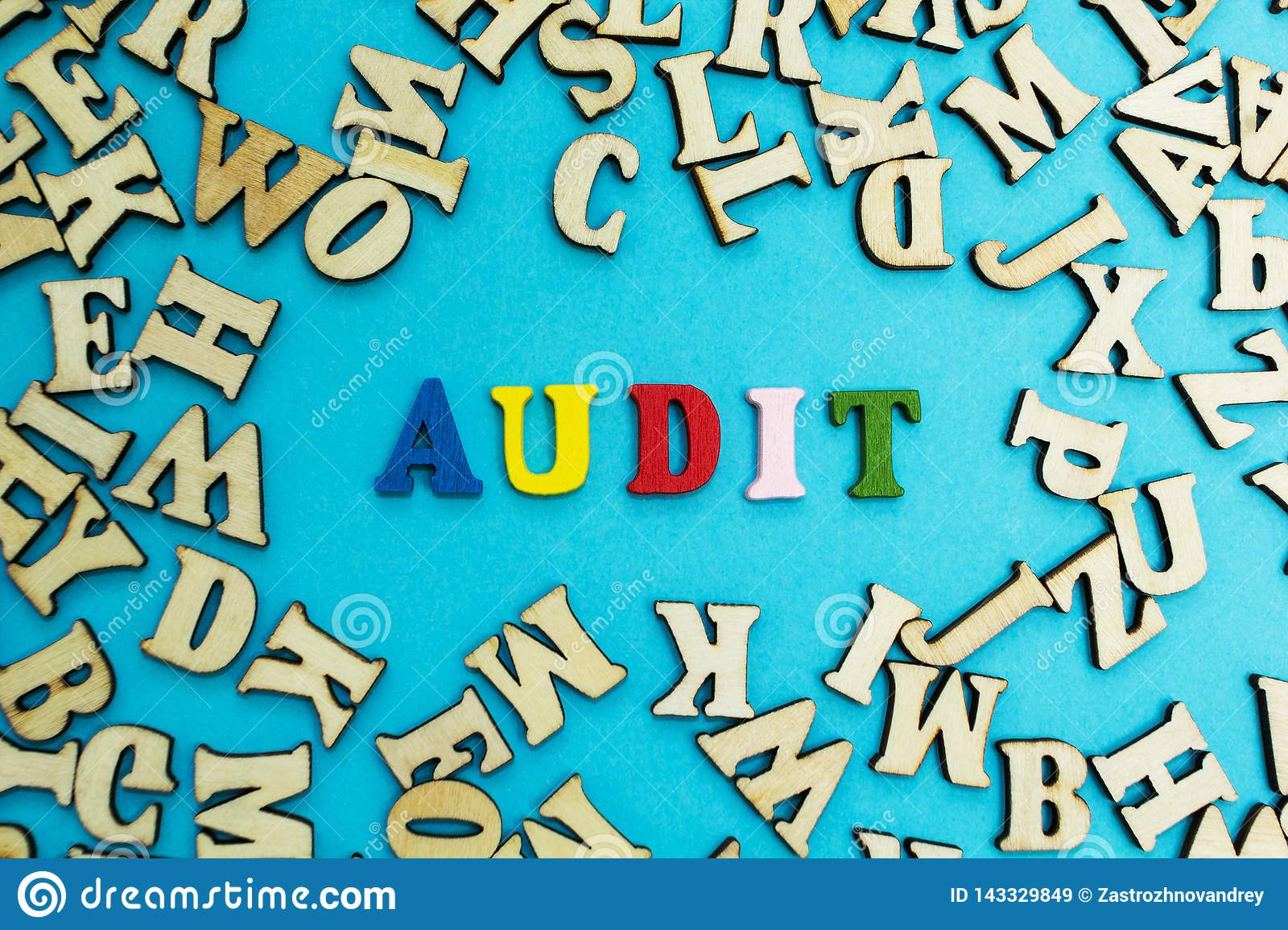 The word `audit` is laid out from multicolored letters on a blue background