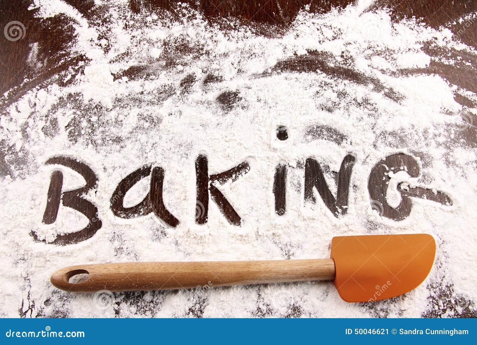 word baking written in white flour on wooden table stock