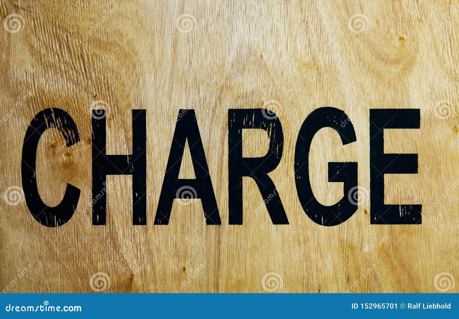 Word charge printed on old brown wood box