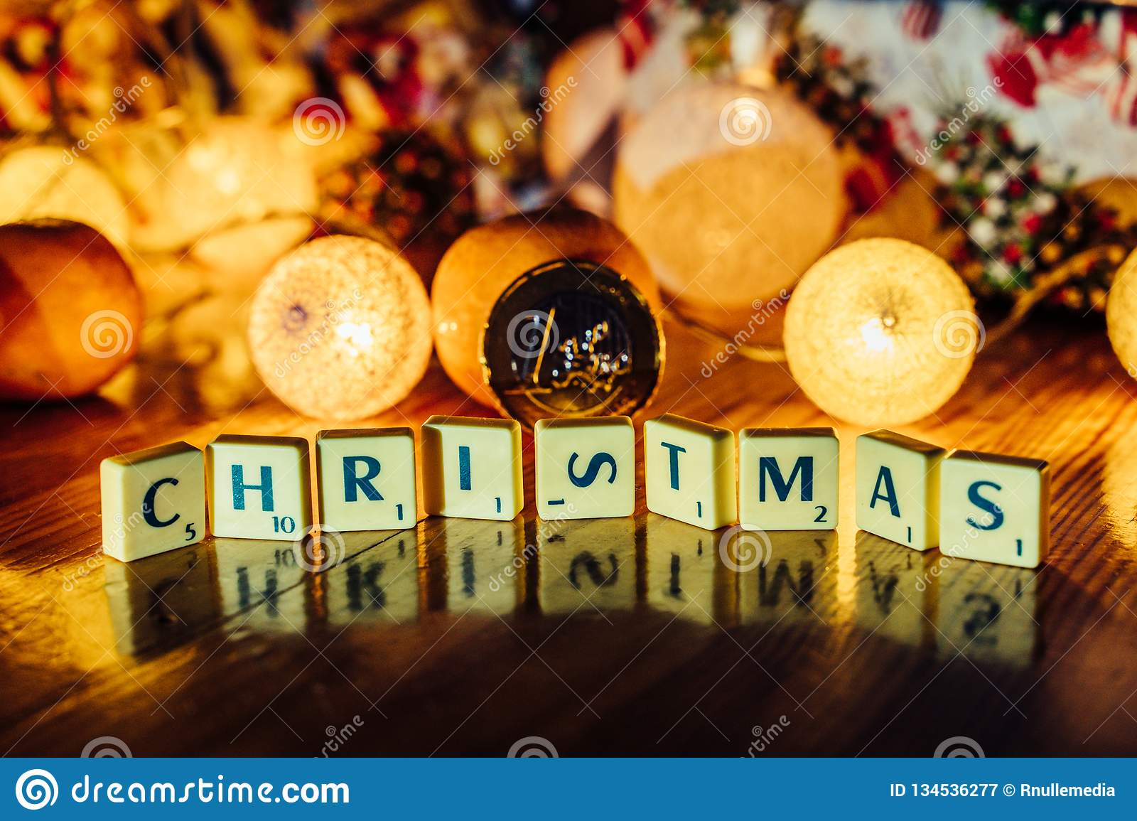 Word \'Christmas\' set on the Wooden Background from Letters of Board Game With the Blurred Christmas Lights, Fruits and Presents. In the Background together royalty free stock photography