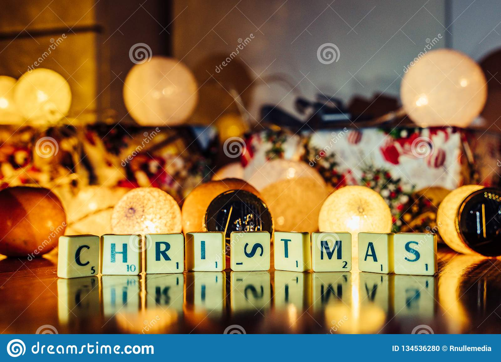 Word \'Christmas\' set on the Wooden Background from Letters of Board Game With the Blurred Christmas Lights, Fruits and Presents. In the Background together stock photo