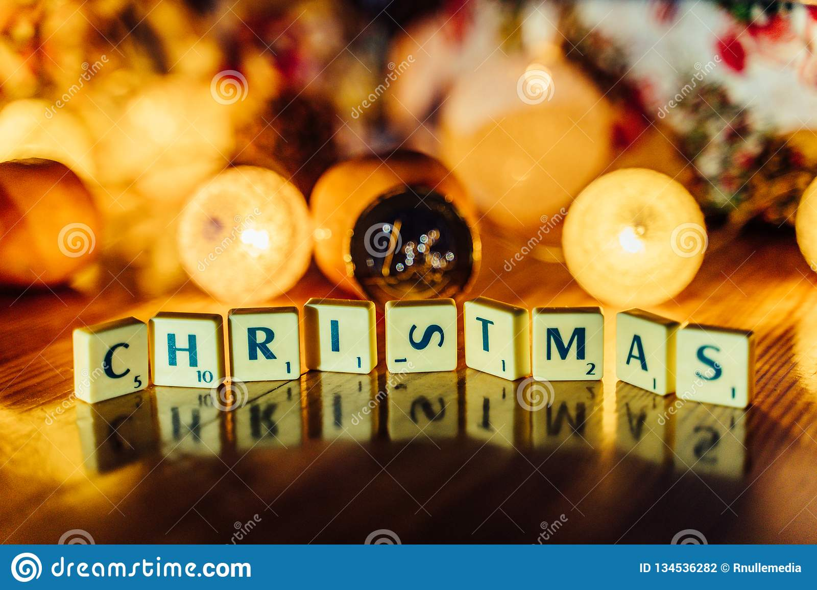 Word \'Christmas\' set on the Wooden Background from Letters of Board Game With the Blurred Christmas Lights, Fruits and Presents. In the Background together stock photography