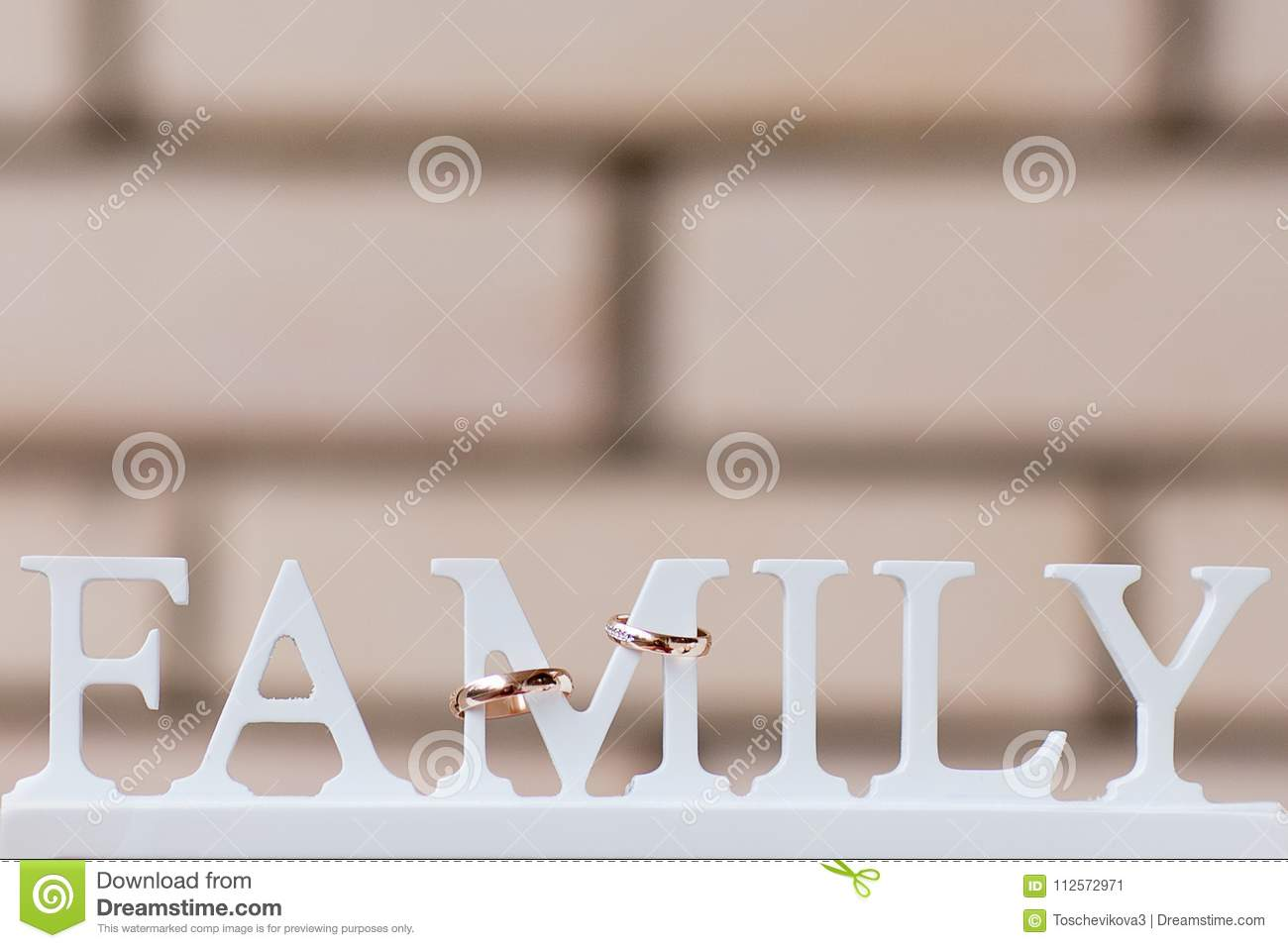 the word family made of white wooden letters and wedding rings on a