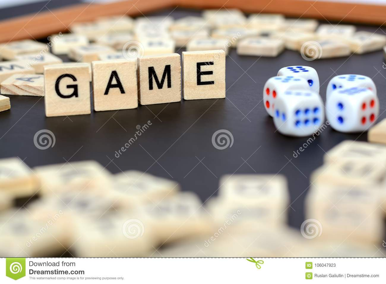 Word Game With Wooden Letters On Black Board With Dice And Letter In