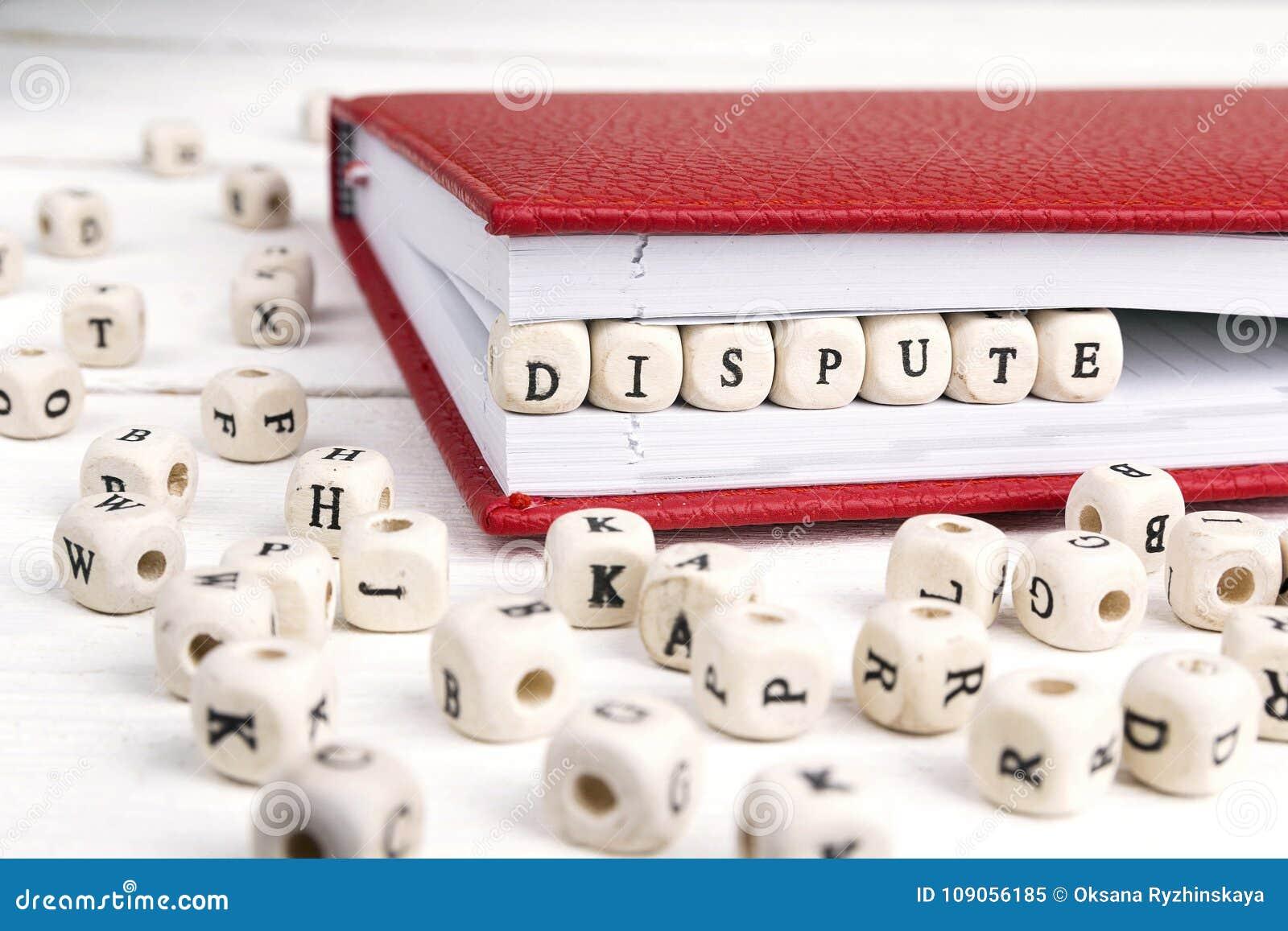 Word Geschil in houten blokken in rood notitieboekje op wit w wordt geschreven dat