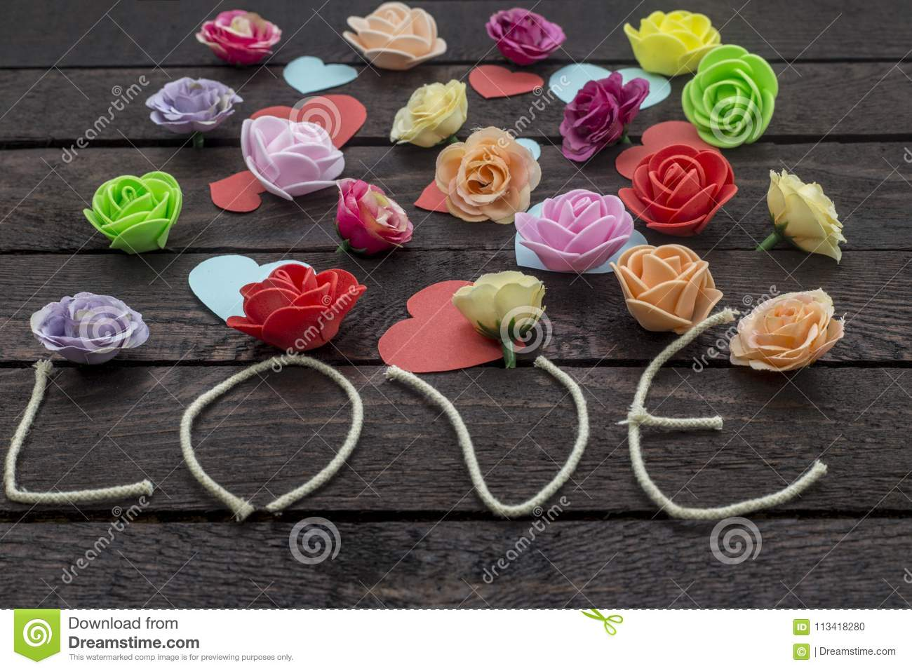 Word Love With Beautiful Flowers On The Brown Background Stock Photo