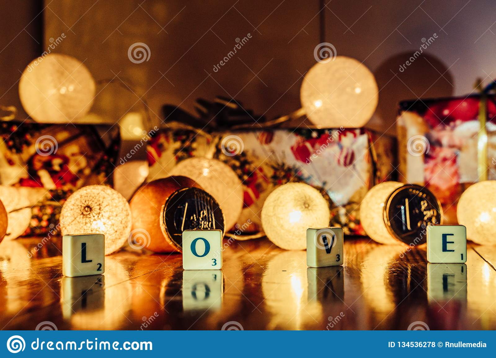 Word \'Love\' set on the Wooden Background from Letters of Board Game With the Blurred Christmas Lights, Fruits and Presents in th. E Background together with royalty free stock photos