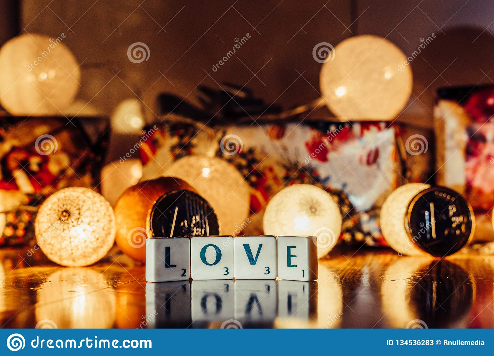 Word \'Love\' set on the Wooden Background from Letters of Board Game With the Blurred Christmas Lights, Fruits and Presents in th. E Background together with stock photos