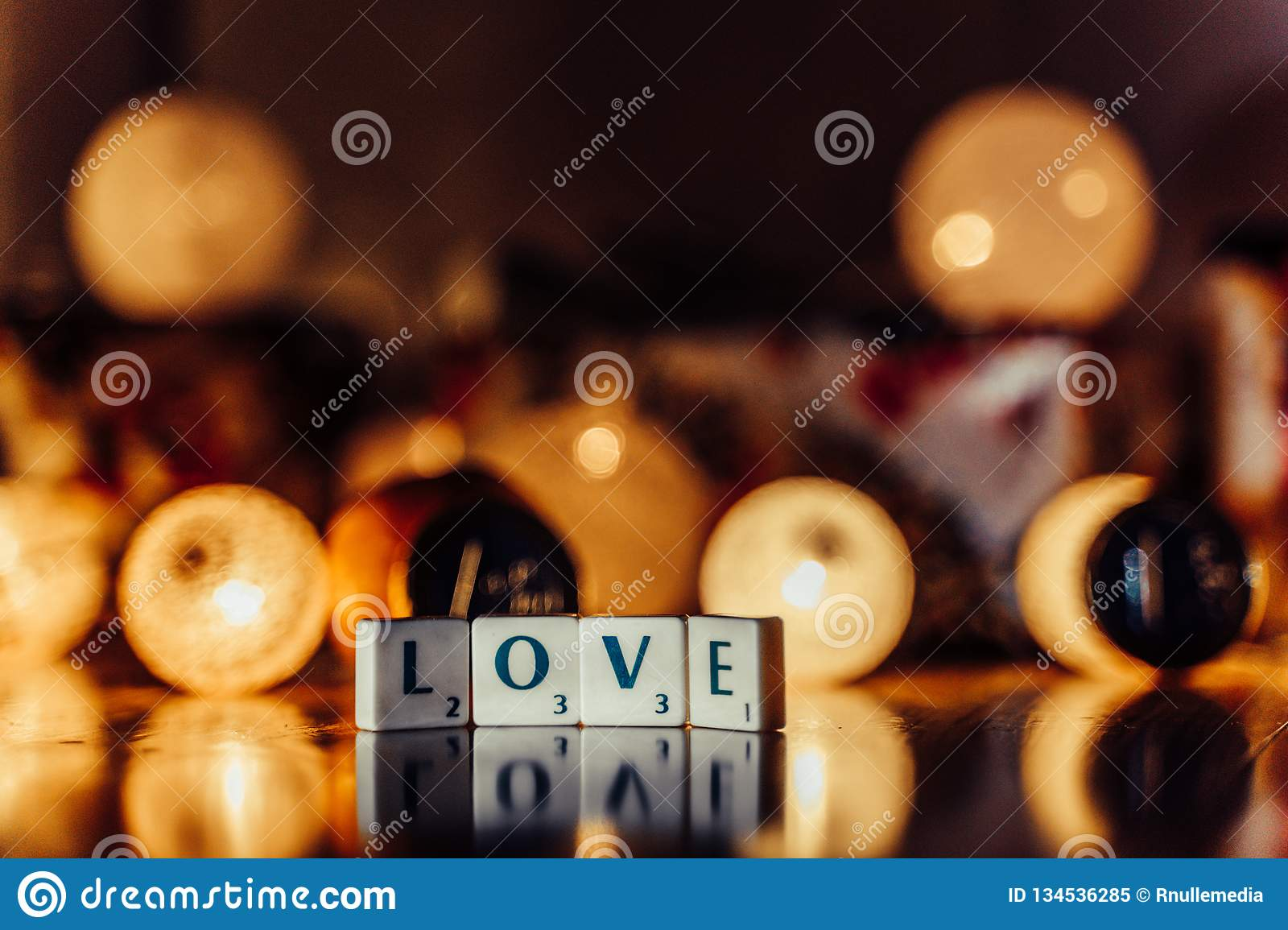 Word \'Love\' set on the Wooden Background from Letters of Board Game With the Blurred Christmas Lights, Fruits and Presents in th. E Background together with royalty free stock photo