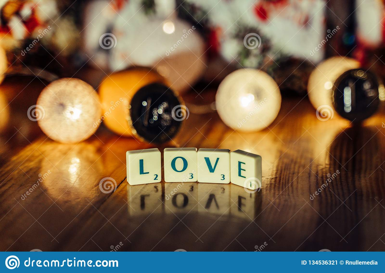 Word \'Love\' set on the Wooden Background from Letters of Board Game With the Blurred Christmas Lights, Fruits and Presents in th. E Background together with stock image