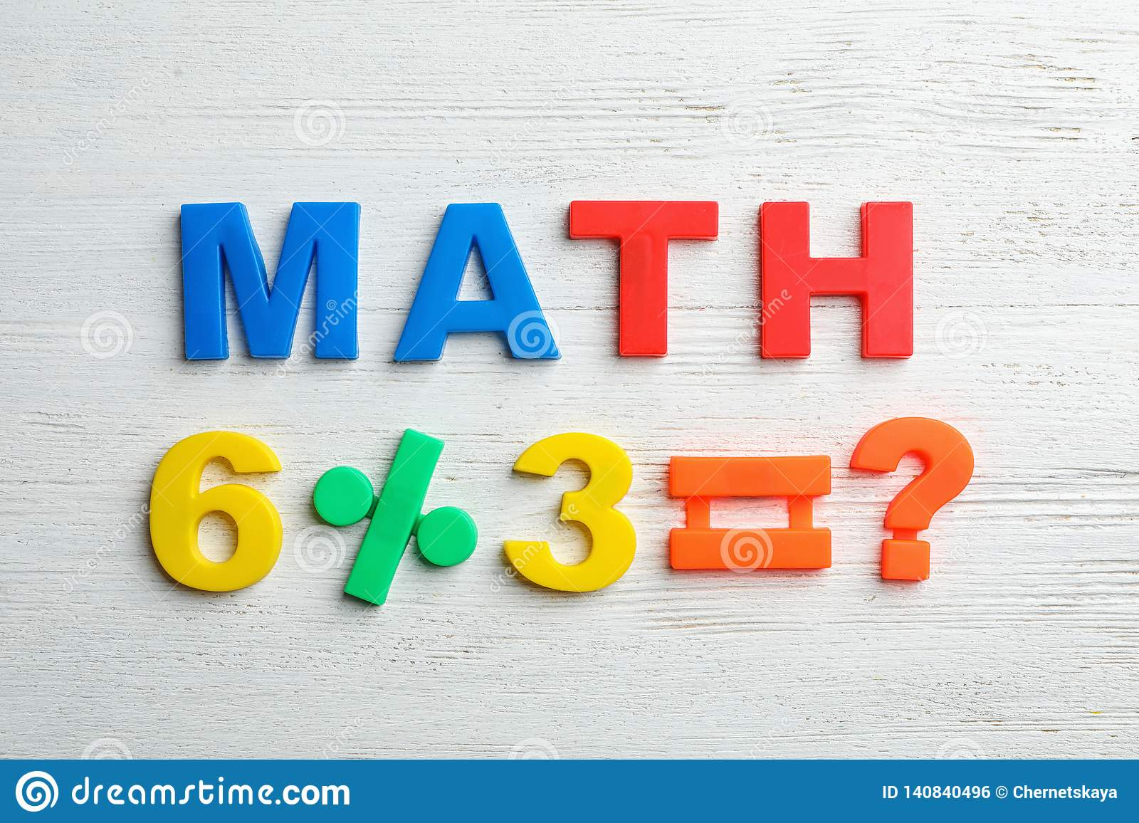 Word MATH and equation of magnetic letters on wooden background
