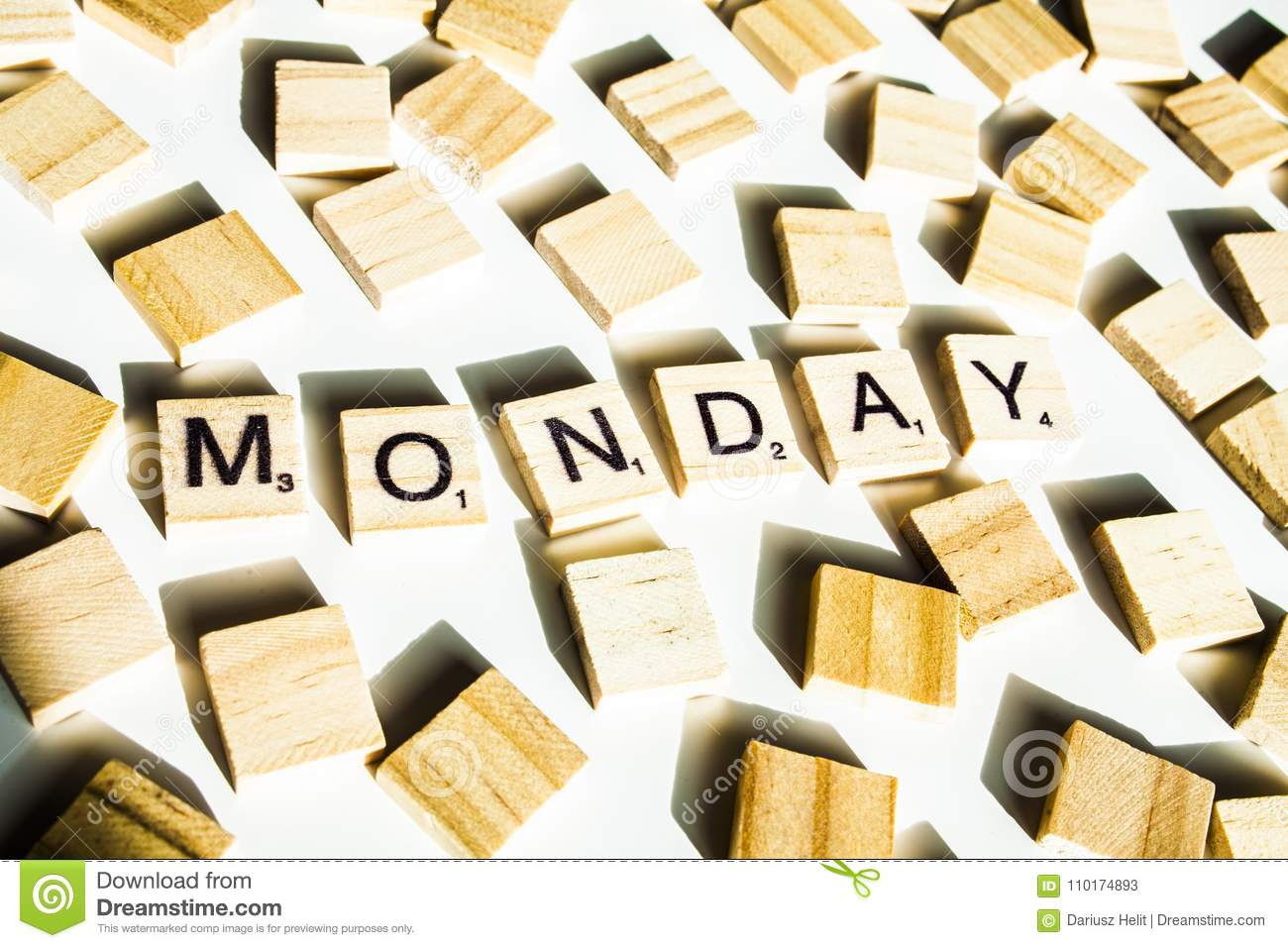 wooden scrabble letters spelling the word monday on white backround