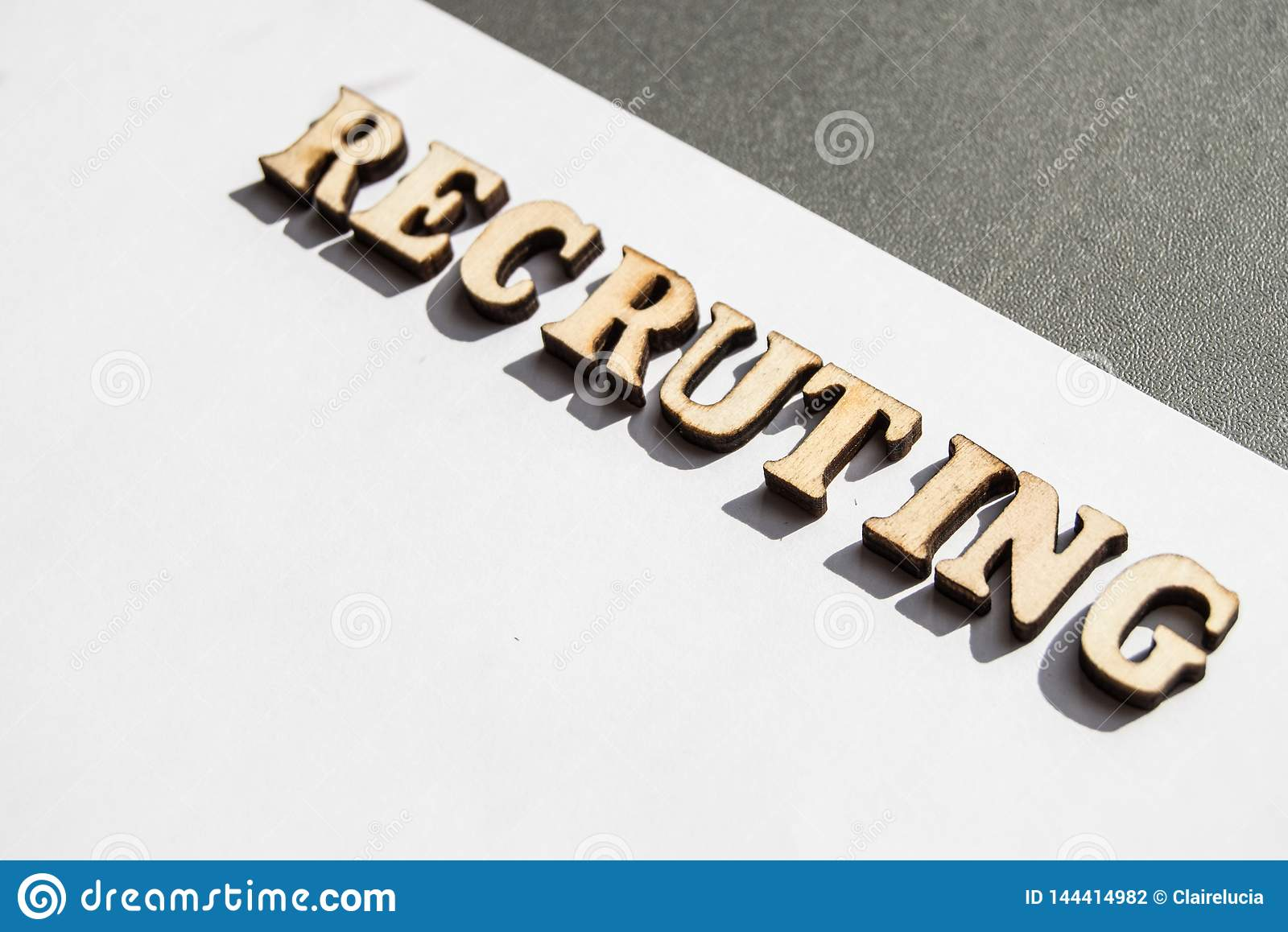 The Word Recruiting Is Written In Wooden Letters On A White