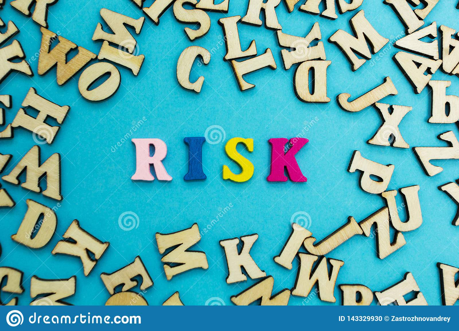 The word `risk` is laid out from multicolored letters on a blue background. Scattered wooden letters