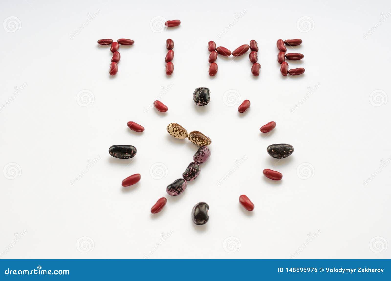 Word tijd en de wijzerplaat vormden uit kleurrijke nierbonen op witte achtergrond Gezond het Eten Concept