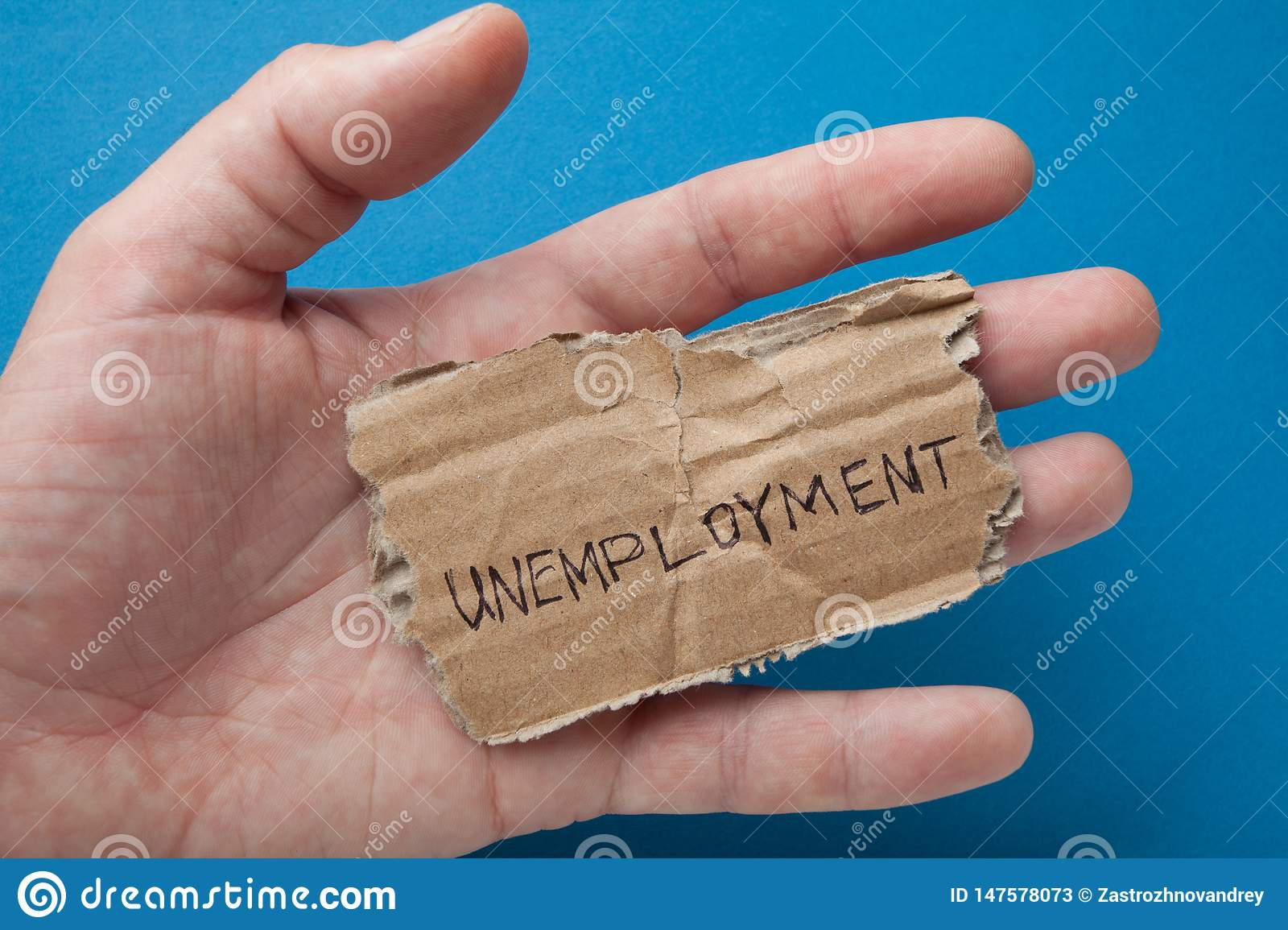 The word `unemployment` on the torn old cardboard in the hand of a man.