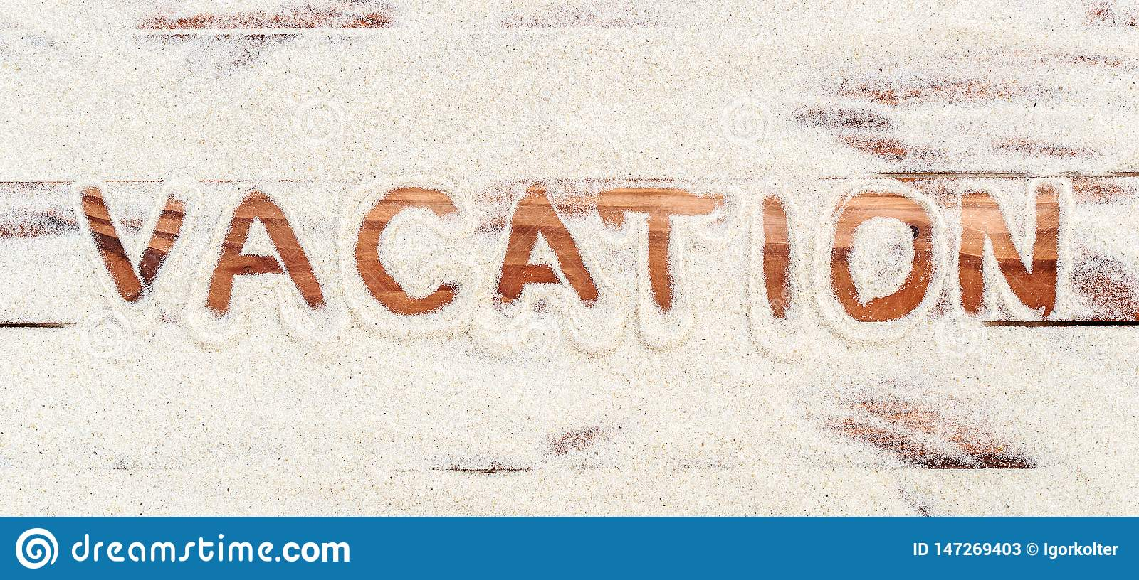 Word `vacation` written by sand on the wooden planks