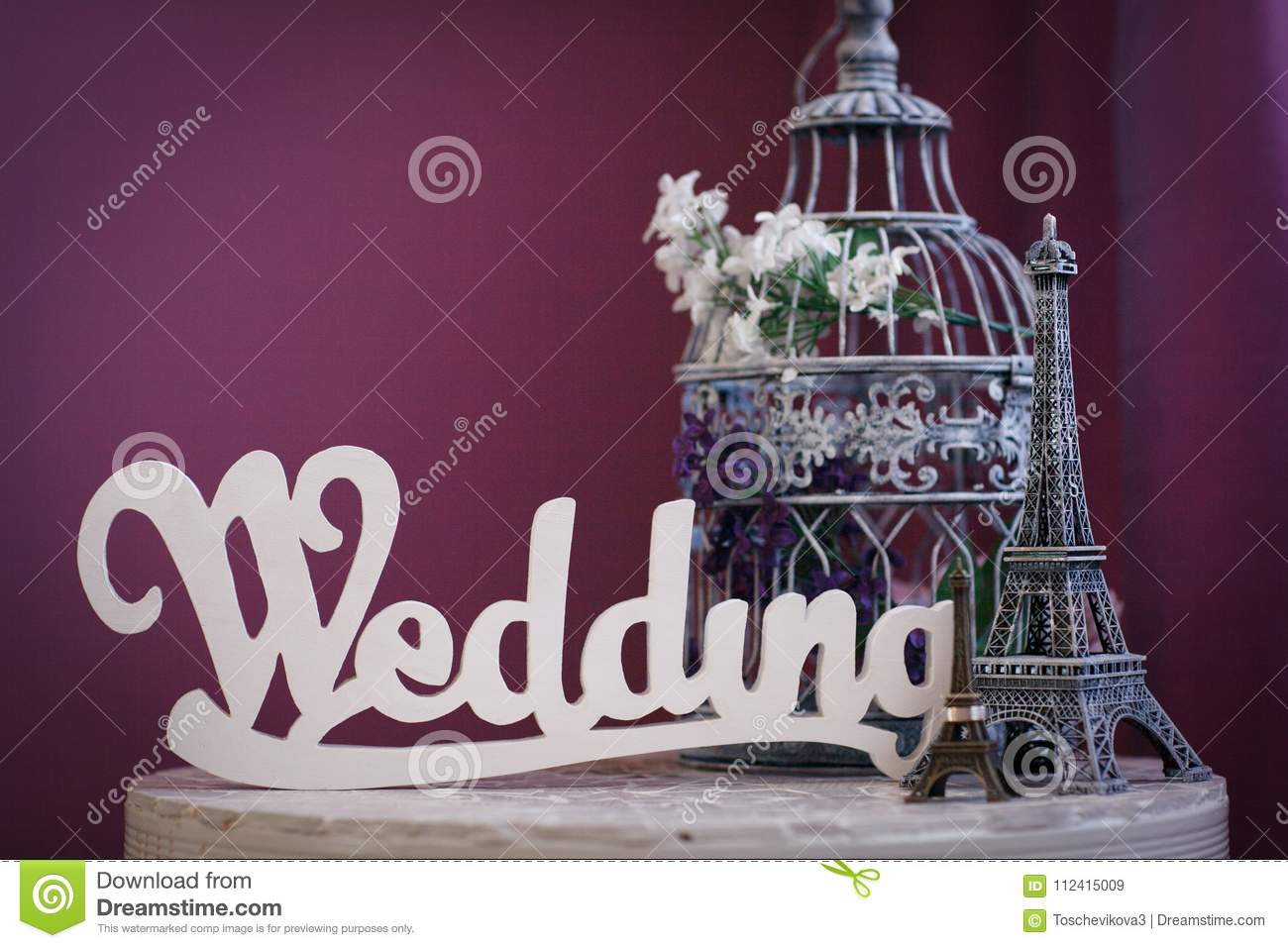 Word `Wedding` made of white wooden letters, statuettes of Eiffel Tower, and cage for birds, stand on table on purple background