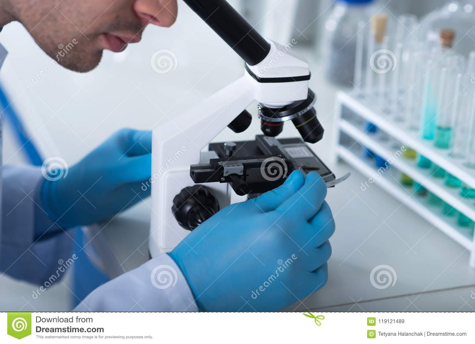 Adult Unshaken Explorer Sitting And Using The Microscope