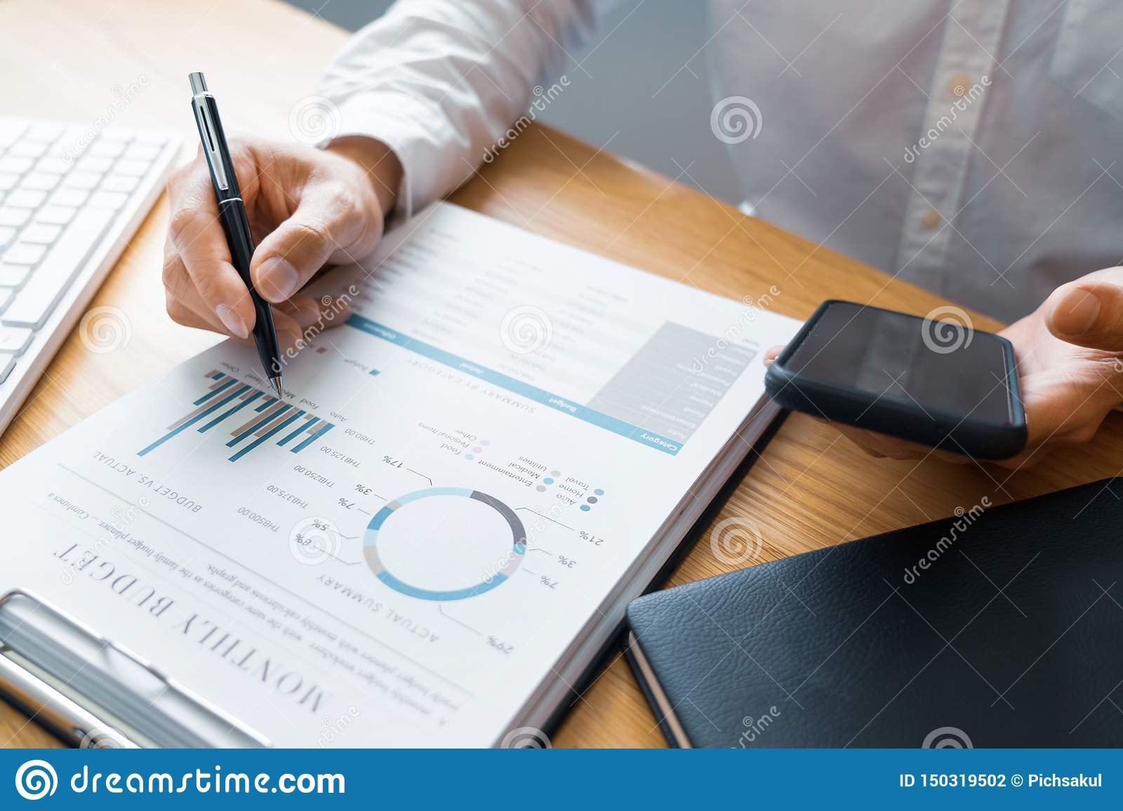 Work process concept, Business man using mobile phone writing in agenda consulting on a desk at home or office