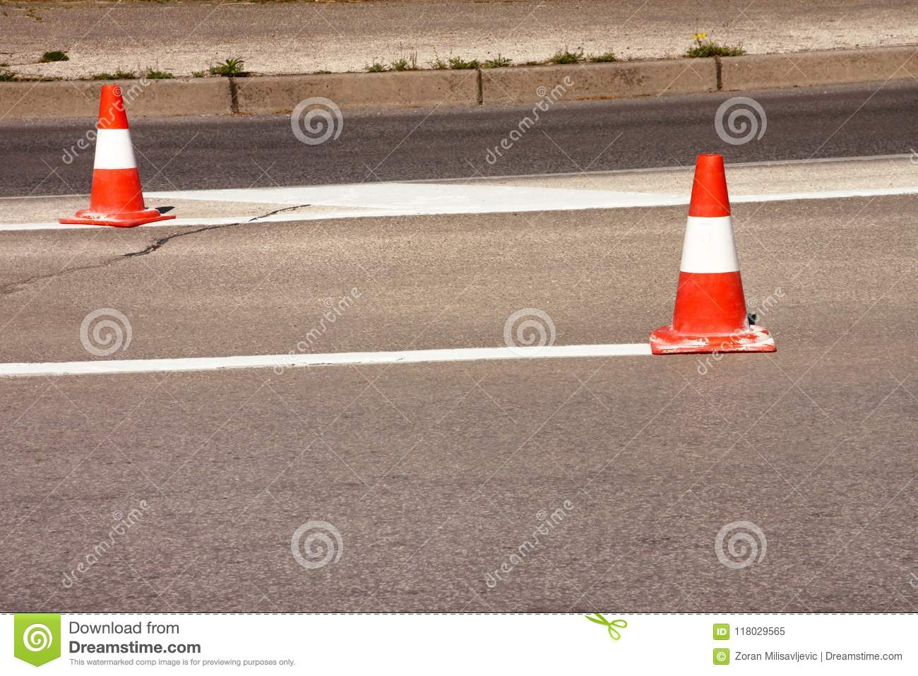 Work on road. Construction cones. Traffic cone, with white and orange stripes on asphalt. Street and traffic signs for signaling.