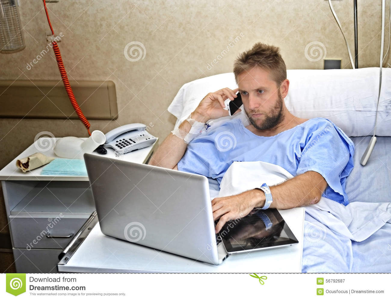 Workaholic business man in hospital room lying in bed sick and injured ...