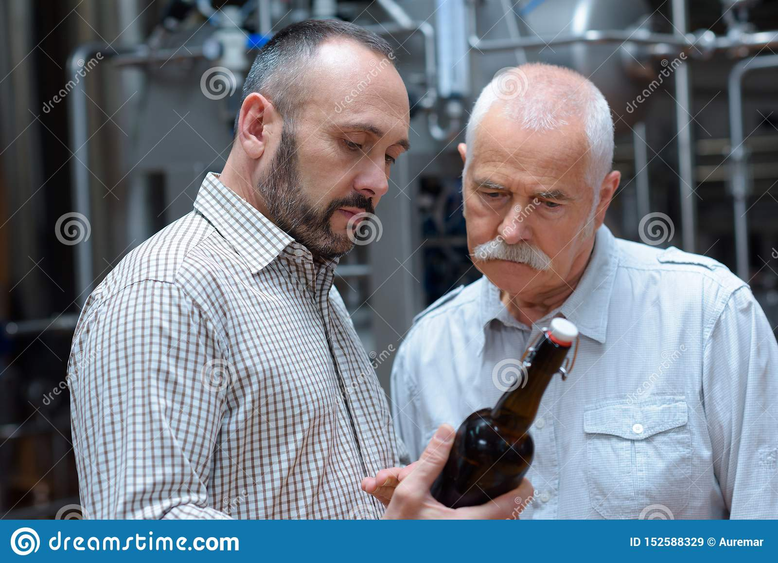 Worker and brewer holding beer bottle in crate at brewery