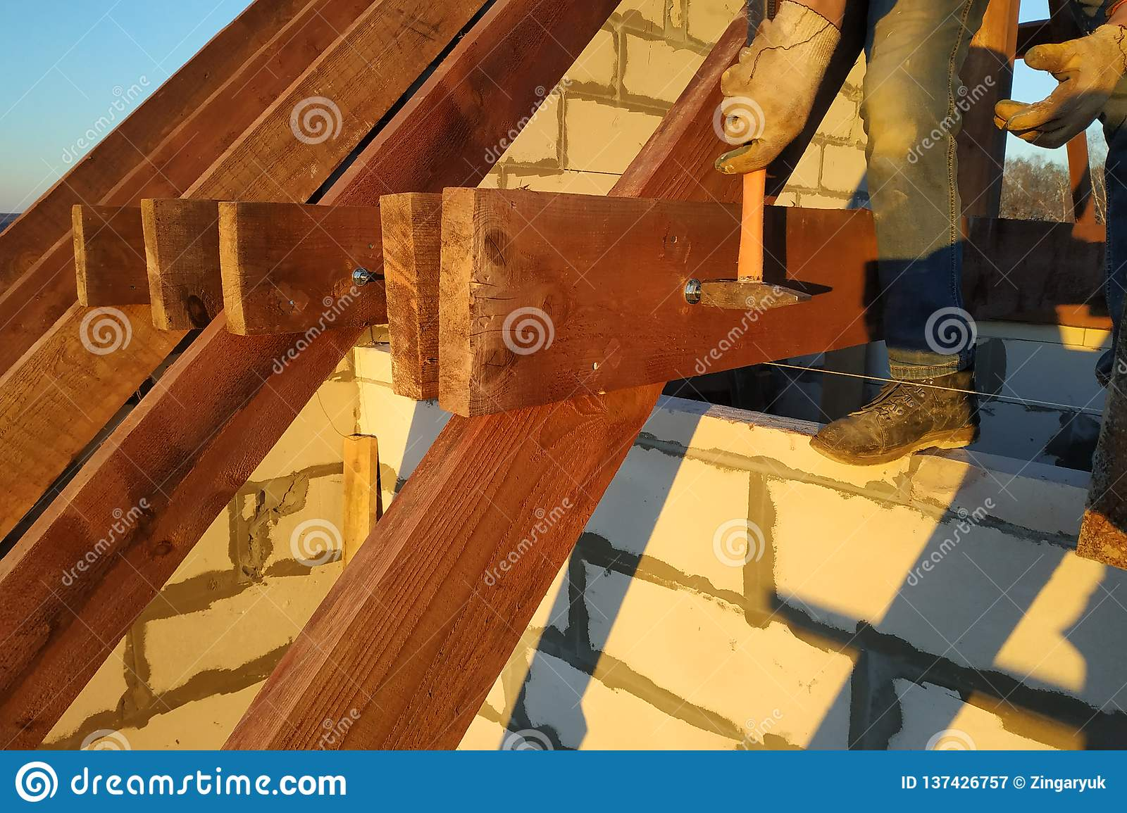 The worker claps the studs with a hammer on the rafters, building a roof