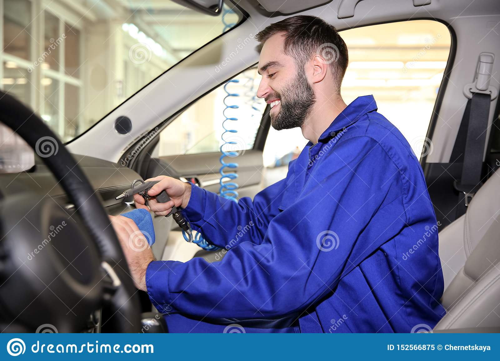 Worker cleaning automobile salon with rag and gun