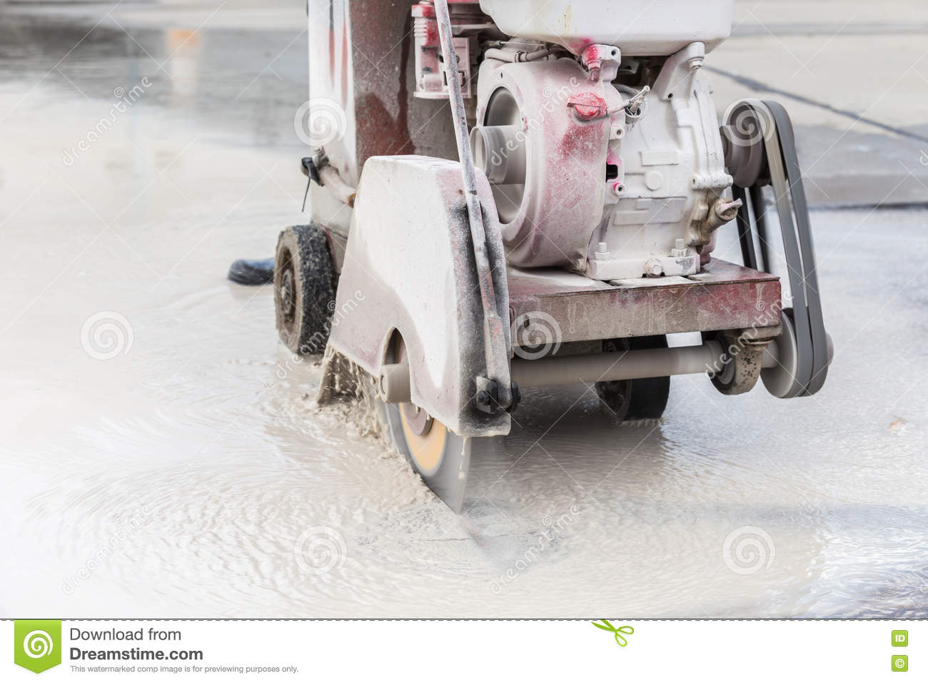 Worker Cutting Concrete Road With Diamond Saw Blade