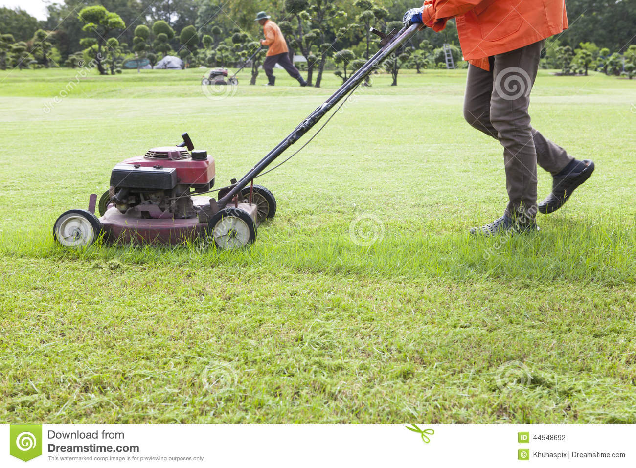 Worker cutting grass field with lawn mower stock photo for Lawn mower cutting grass