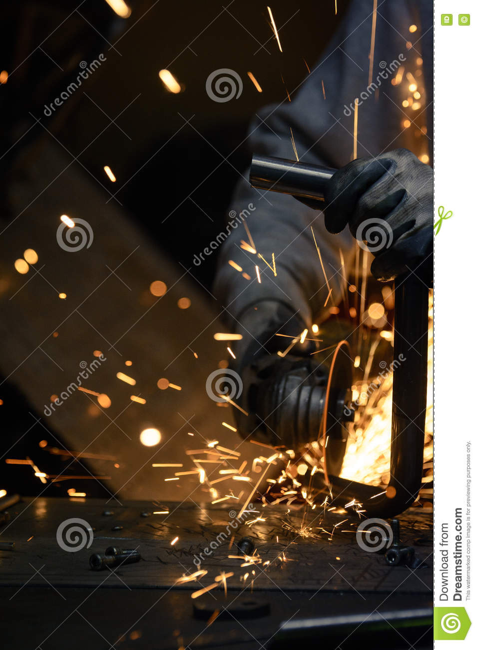 Worker cutting metal with grinder sparks flying while