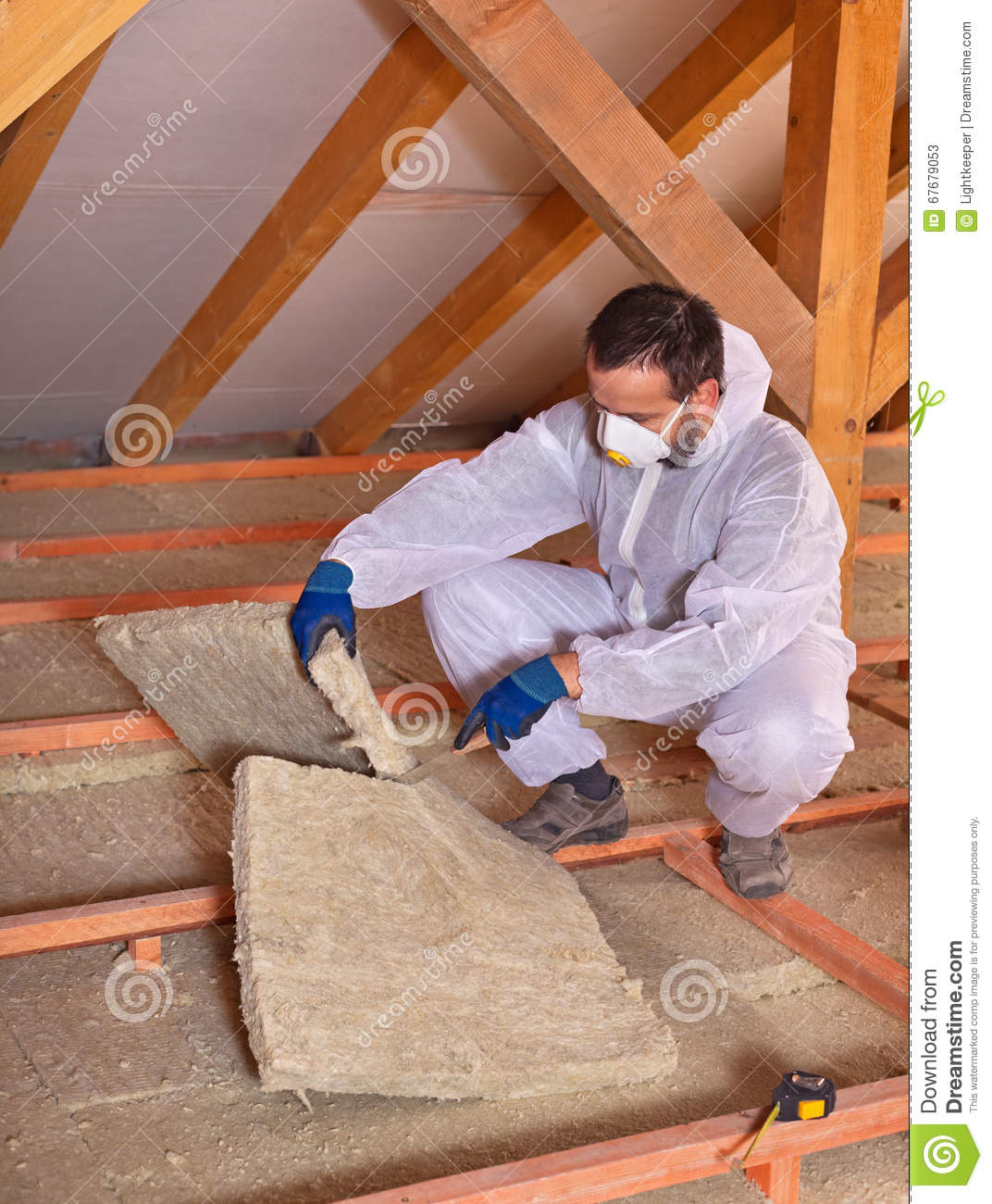 Worker cutting mineral wool panel to install thermal for Mineral wool installation