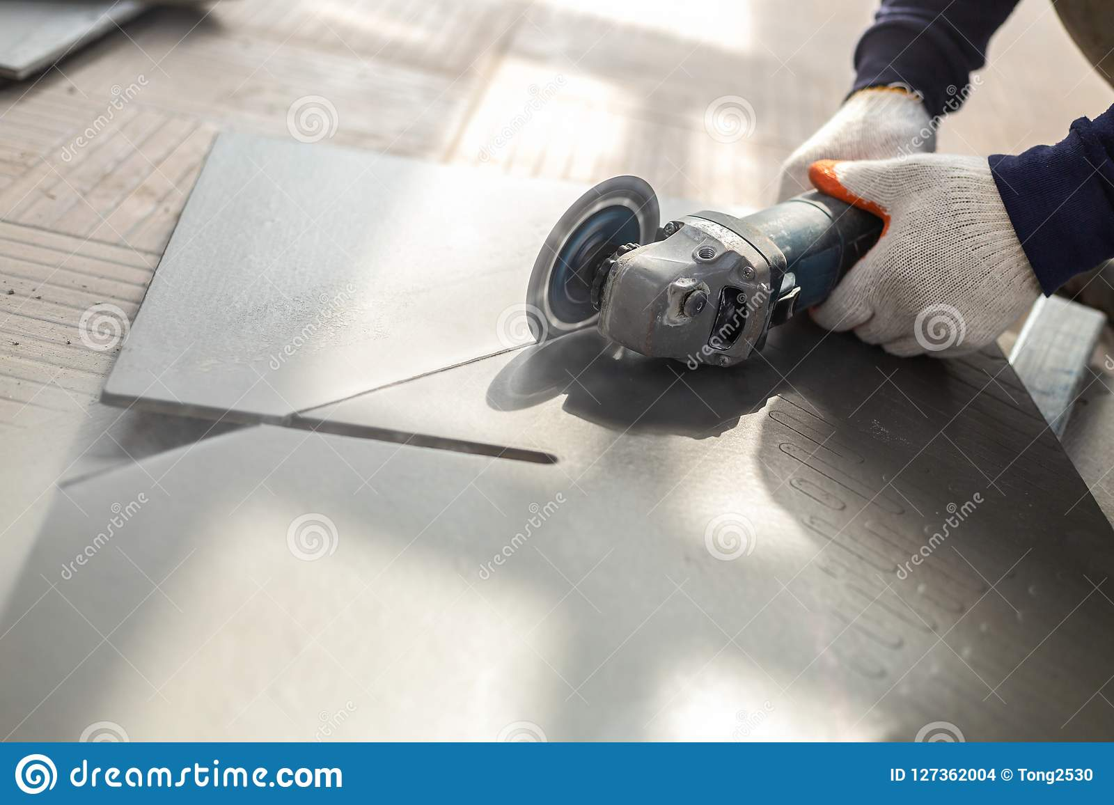 Worker Cutting A Tile Using An Angle Grinder At Construction Sit