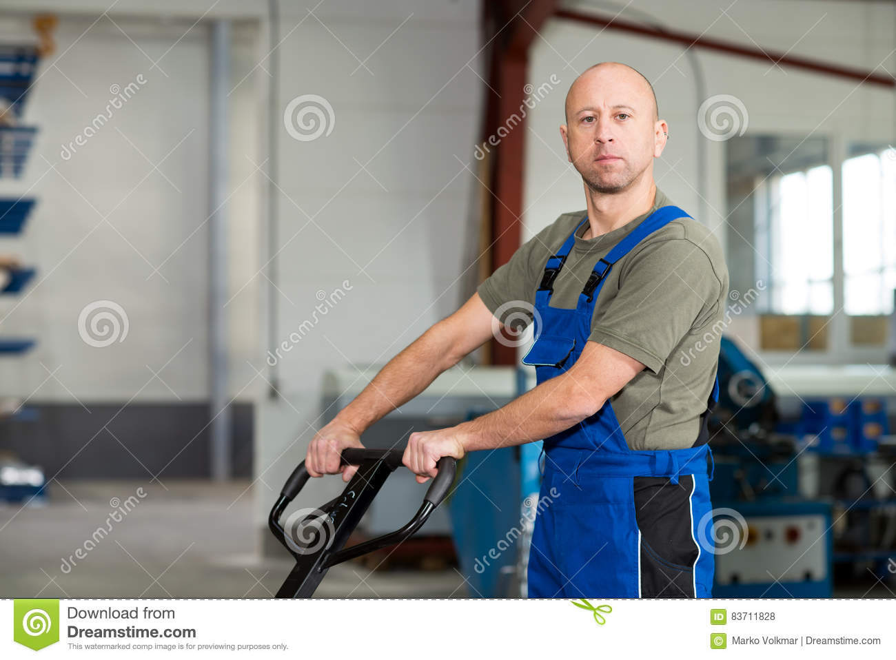 Worker In Factory With Hand Lift Stock Photo