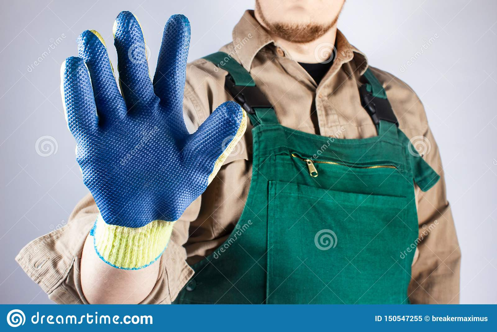 Worker in green overall outfit showing blue glove