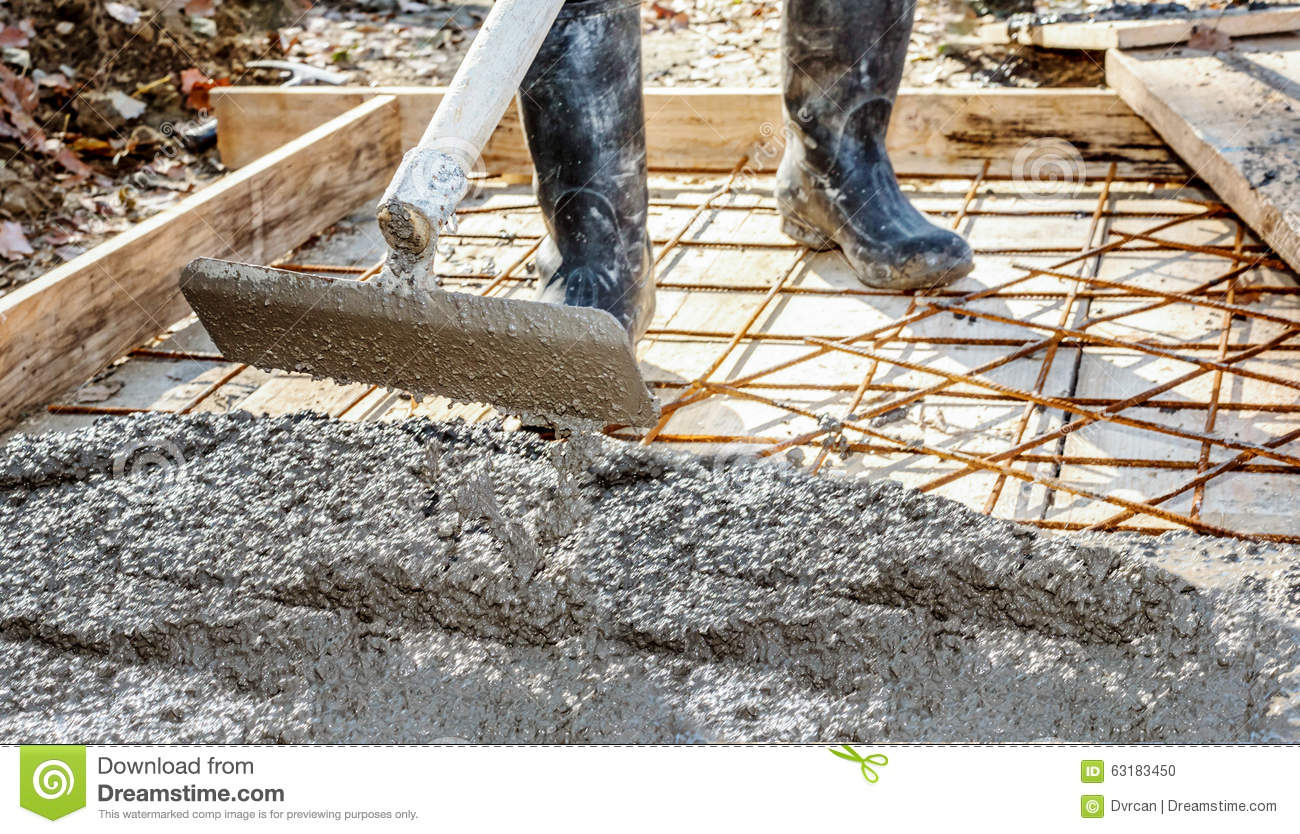 worker with gum boots spreading ready mix concrete stock. Black Bedroom Furniture Sets. Home Design Ideas