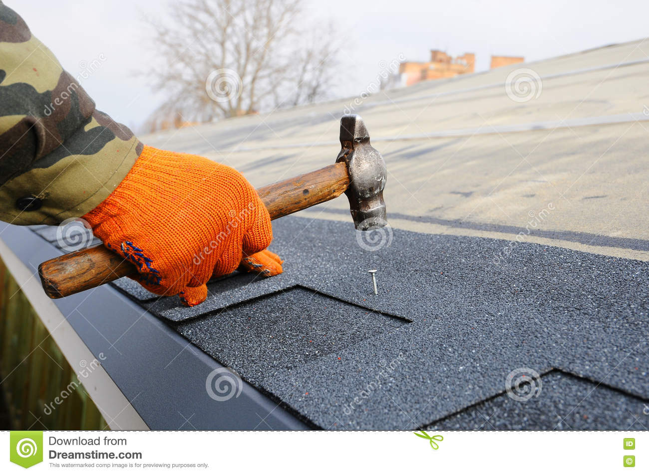 Worker hands installing bitumen roof shingles. Worker Hammer in Nails on the Roof. Roofer is hammering a Nail in the Roof Shingles