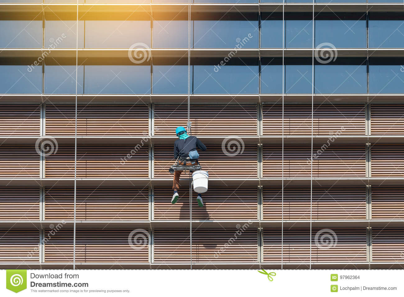 Worker hanging outside high rise building cleaning window and mirror.