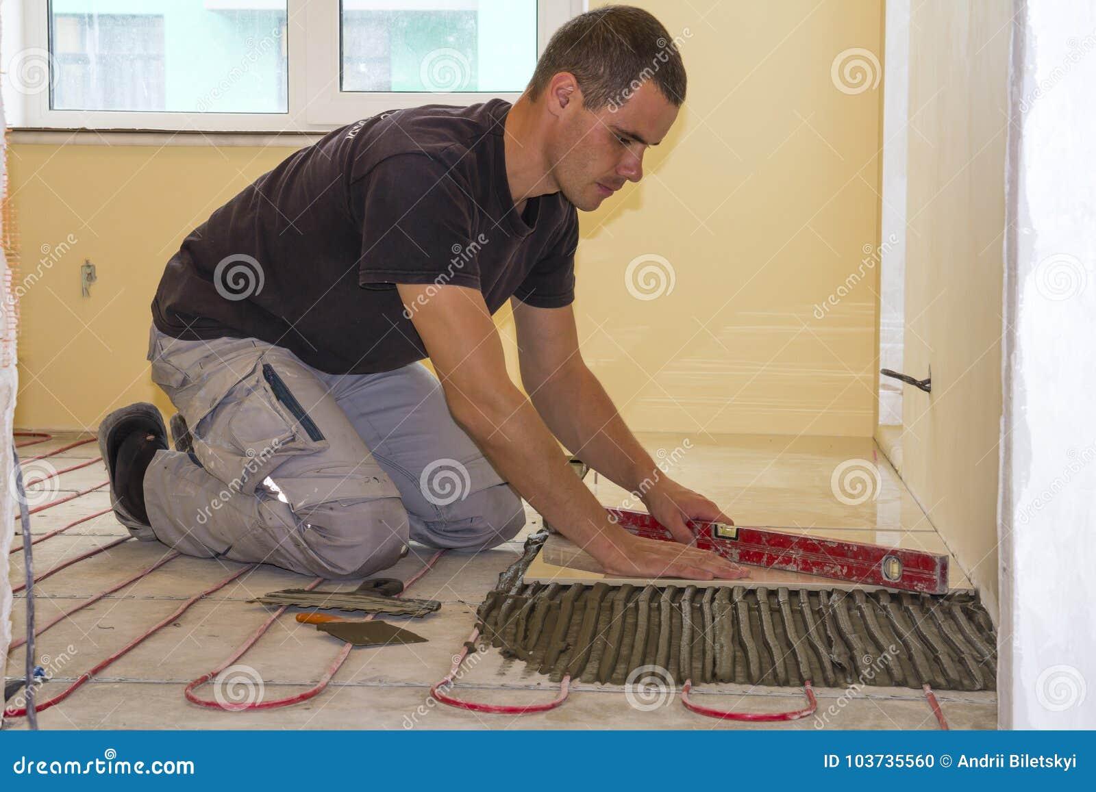 Worker installing floor tiles ceramic tiles and tools for tiler worker installing floor tiles ceramic tiles and tools for tiler royalty free stock photo download worker installing floor tiles dailygadgetfo Images