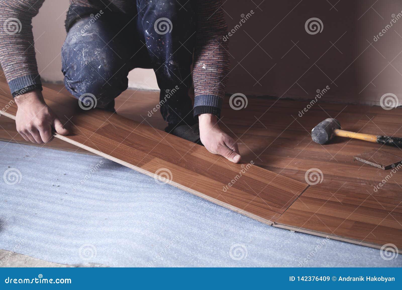 Worker installing new laminate wooden floor
