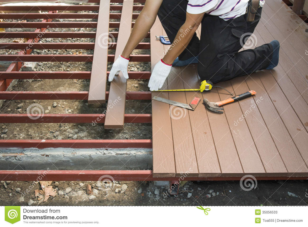 Worker Installing Wood Floor For Patio Stock Photos