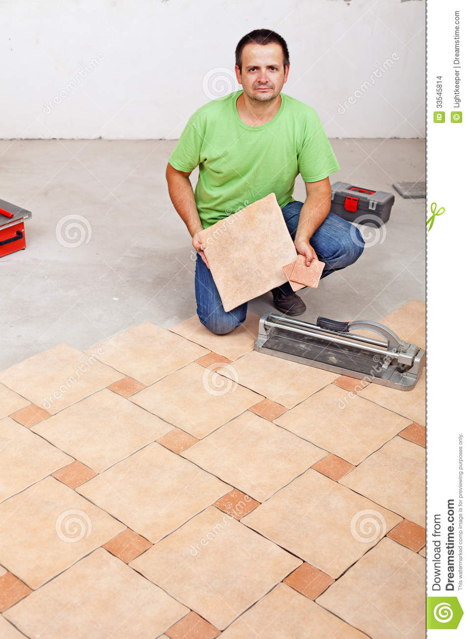 Worker laying floor tiles on concrete surface stock photo image worker laying floor tiles on concrete surface dailygadgetfo Gallery