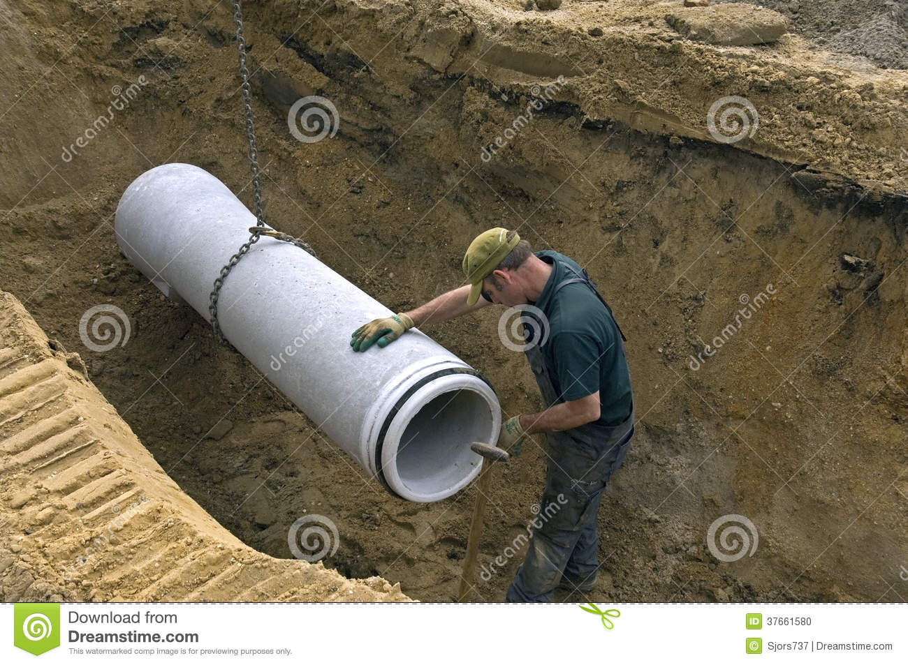 Worker laying new sewer pipe in slot in the street for Sewer drain pipe