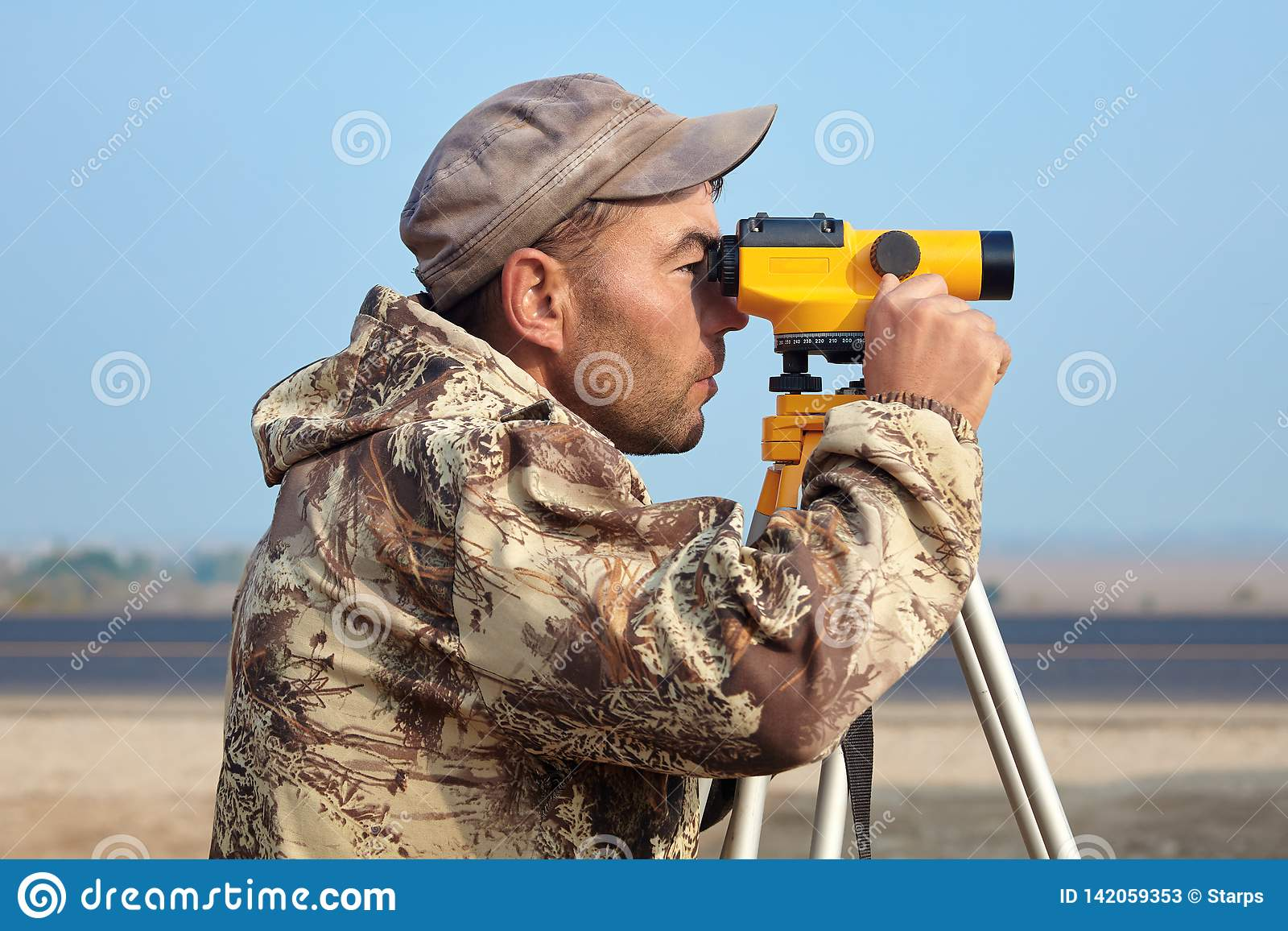 Worker with level, surveyor builder with geodesy equipment close to highway, with mobile phone, smiling.