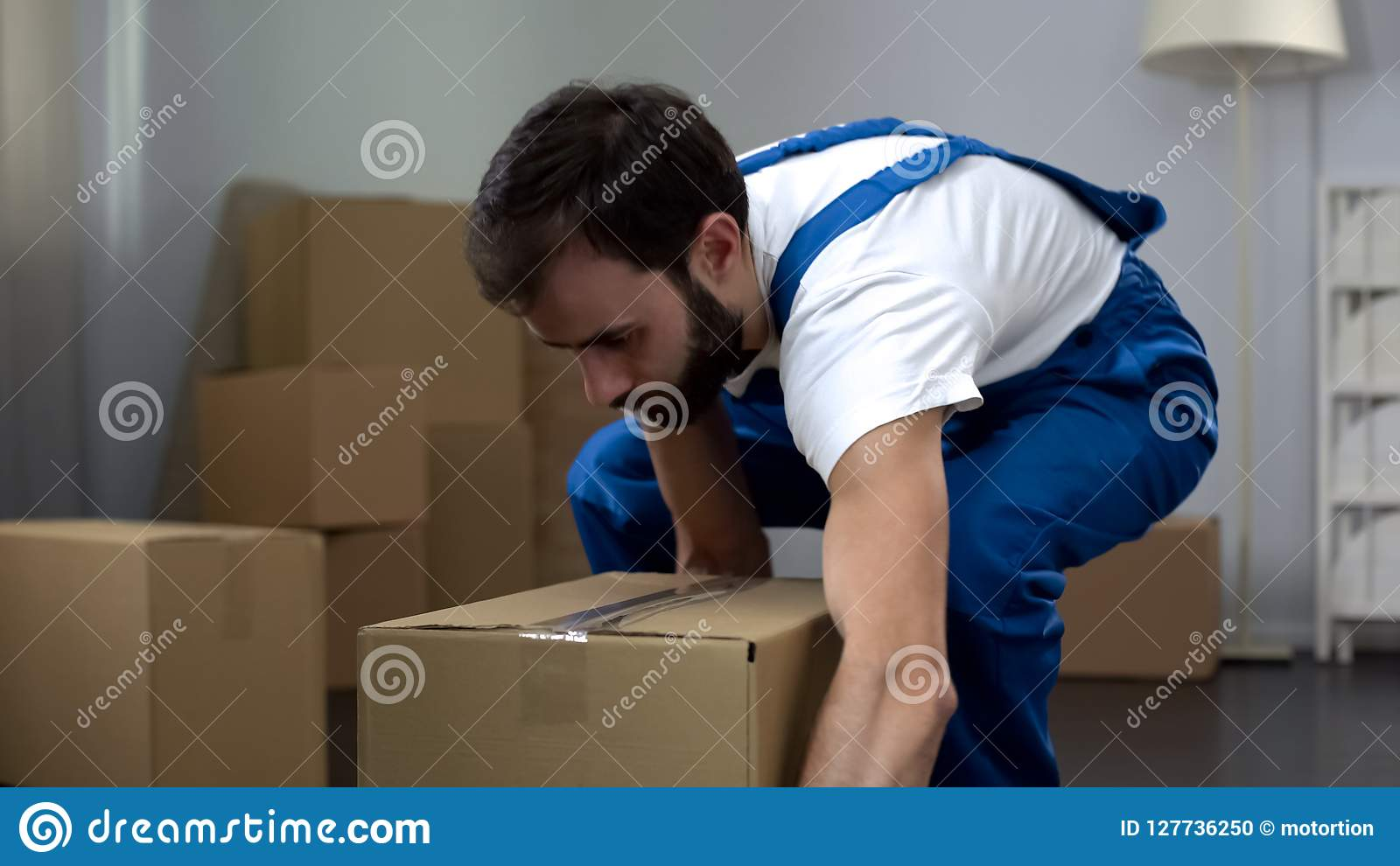 Worker from moving company carrying cardboard box, quality relocation services