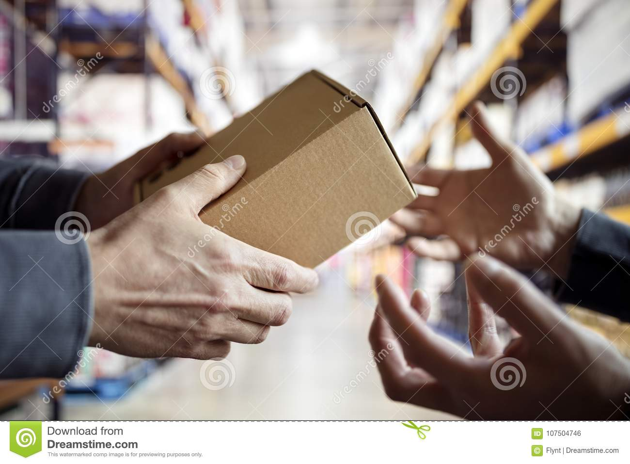 Worker with package in a distribution warehouse