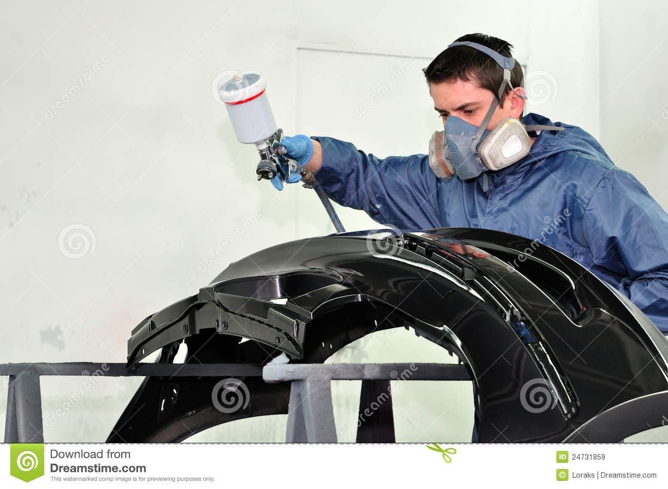 Worker painting a fender.