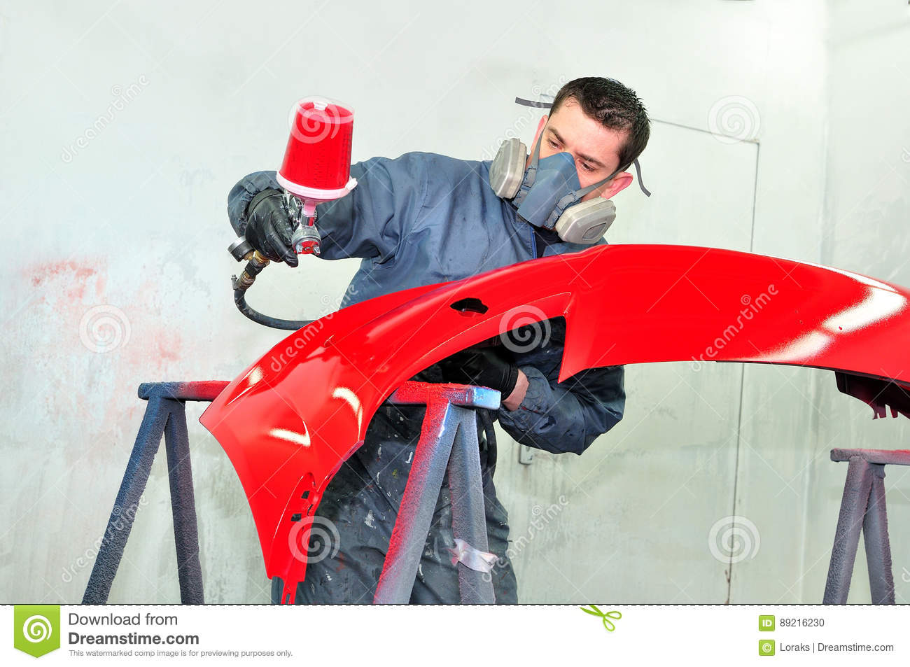 Worker painting red car bumper.